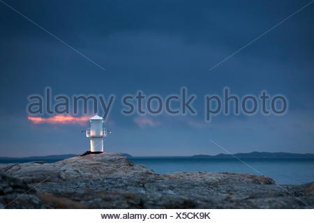 Sweden, Bohuslan, Marstrand, Lighthouse on rocks at dusk - Stock Photo