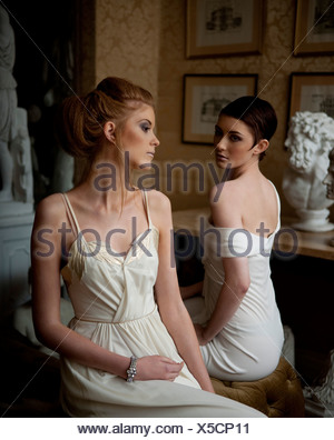 Two young women dressed in white, sitting - Stock Photo