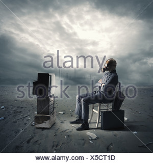 businessman with gas mask watching TV - Stock Photo