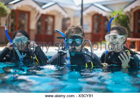Three young adult scuba divers training in swimming pool - Stock Photo