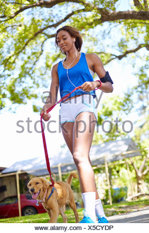 Young woman exercising with dog in park - Stock Photo