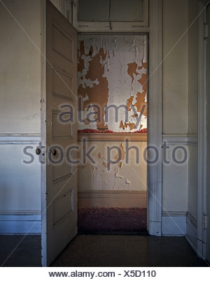 Paint peeling from wall seen through doorway - Stock Photo