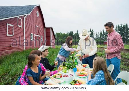 Multi-generation family enjoying dinner outside barn - Stock Photo
