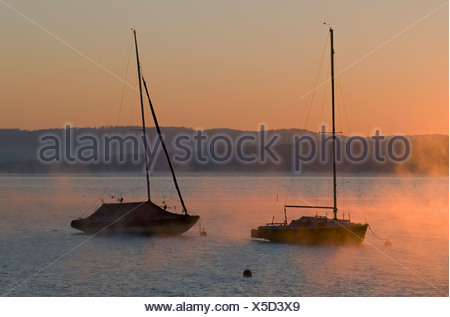 Sailing boats and low morning fog over Ammersee lake at Utting, Bavaria, Germany, Europe - Stock Photo