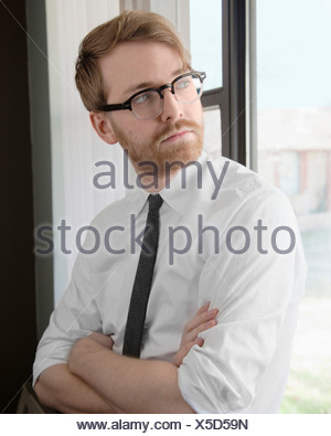 Young man wearing spectacles and tie looking away - Stock Photo