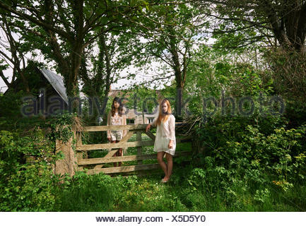 Portrait of two young women standing gazing from field gate - Stock Photo