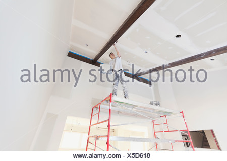 Low angle view of tradesman plastering drywall in home - Stock Photo