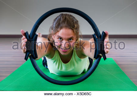 A young woman is training Pilates, holding and looking through the ring, Germany - Stock Photo