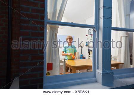 Boy in living room viewed through window - Stock Photo
