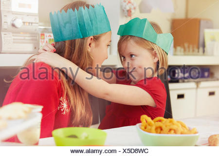 Sisters in paper crowns, hugging - Stock Photo