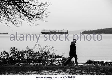 Man in a touque walking through small patch of snow along oceans edge, past freighters and branches. - Stock Photo
