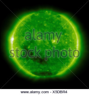 The dark coronal hole in Sun's lower region is 'open' magnetic area through which solar wind follows seen in this view Solar - Stock Photo