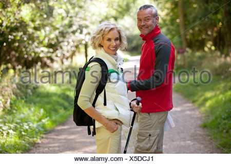 A mature couple standing on a country path smiling, close up - Stock Photo