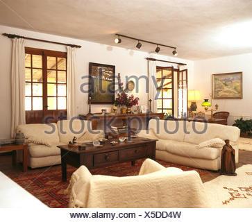 Cream sofas and dark wood coffee table in living room of Spanish villa - Stock Photo