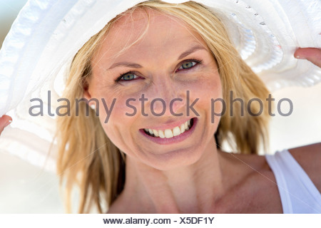 Close up portrait of smiling woman in sun hat - Stock Photo