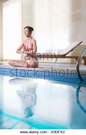 Woman meditating in lotus pose and meditating at poolside - Stock Photo
