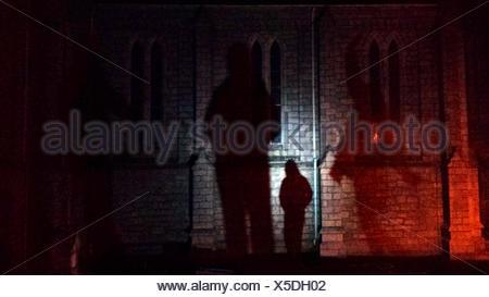 Man Figure Casting Shadow On Church Wall - Stock Photo