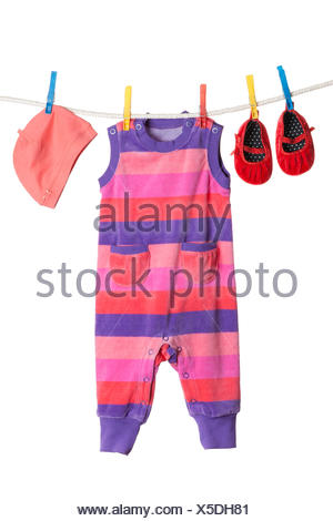 A set of children's clothes hanging on a clothesline. - Stock Photo