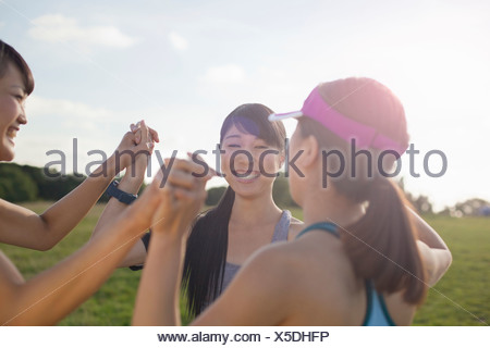Three young female runners getting ready to run - Stock Photo