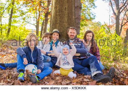 Portrait of family sitting in forest, beside tree - Stock Photo