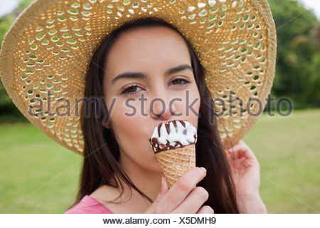 Young woman standing in a park while wearing a hat and eating an ice cream - Stock Photo