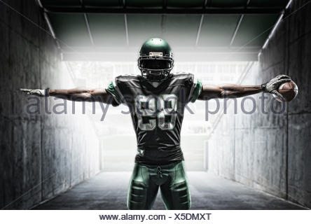 Football player holding ball - Stock Photo