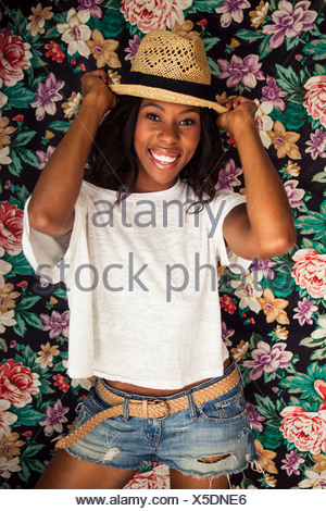 Young woman wearing straw hat in front of floral wallpaper - Stock Photo