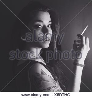 Portrait Of A Young Woman Smoking Over Plain Background - Stock Photo