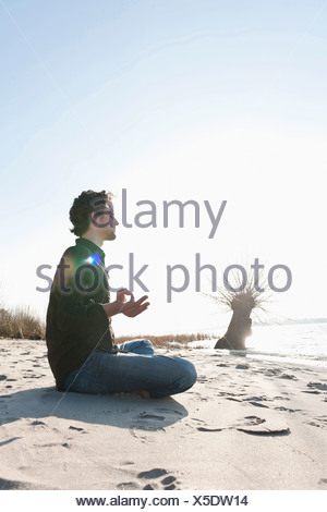Germany, Hamburg, Mid adult man doing yoga near Elbe river - Stock Photo