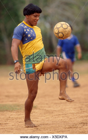 Acculturated Brazilian indian Yaulapiti indigenous people play soccer and wears Brazil soccer team shirt and watch Xingu Amazon - Stock Photo