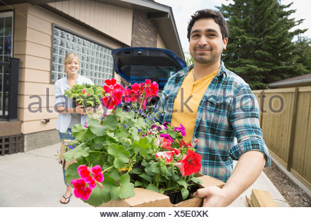 Portrait of couple unloading flowers from car - Stock Photo