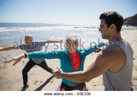 Crossfit trainer helping senior couple exercising, practicing yoga warrior 2 pose on sunny beach - Stock Photo