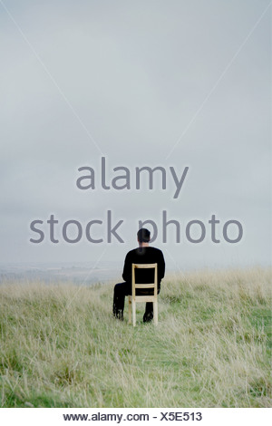 man sitting on a chair on a hillside enjoying the view - Stock Photo