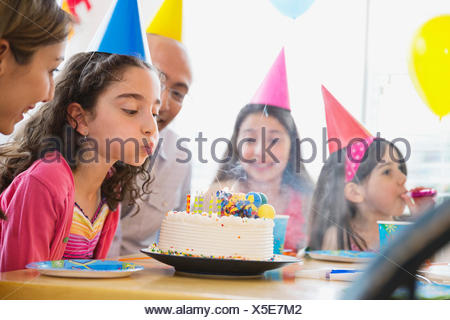 Little girl blowing out candles at birthday party - Stock Photo
