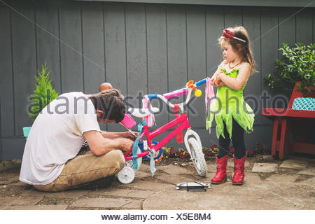 Father mending his daughter's bicycle - Stock Photo