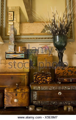 Urn with porcupine quills on collection of antique boxes - Stock Photo