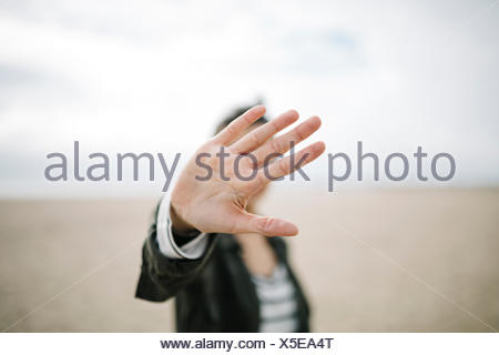 Young woman hiding face behind her outstretched hand - Stock Photo