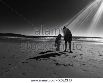 Mother With Her Daughter Standing On Beach - Stock Photo