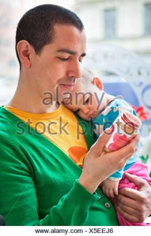Father holding daughter (0-11 months) and reading on a jar - Stock Photo