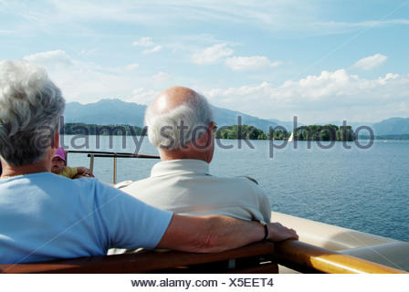 People on a ferry (Weisse Flotte) on Chiemsee. At the background: island Herreninsel (on Herreninsel you´ll find the castle - Stock Photo