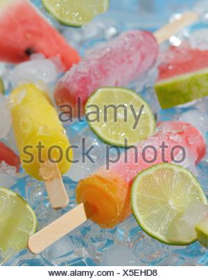 Refreshing lime and fruits ice pops on ice cubes. - Stock Photo