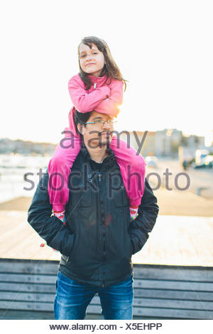 Father carrying daughter (10-11) on shoulders - Stock Photo