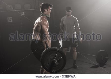 Mid adult man lifting barbell, while trainer looks on - Stock Photo
