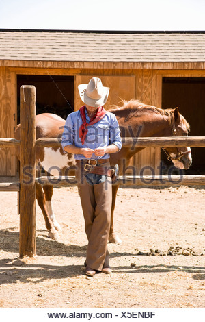 A cowboy leaning against a fence on a ranch - Stock Photo