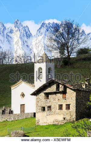 Alpine church and green meadows framed by the snowy peaks in spring Daloo Chiavenna Valley Valtellina Lombardy Italy Europe - Stock Photo
