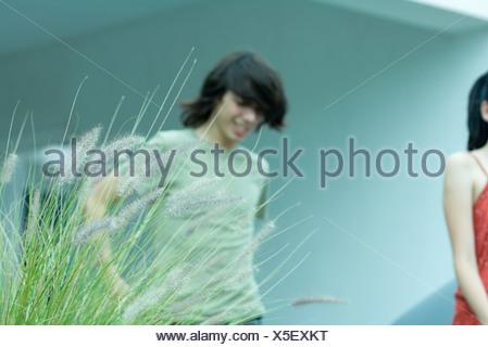 Teenage boy and teenage girl walking outdoors, cropped view - Stock Photo