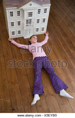 A girl lying in front of her dollhouse. - Stock Photo