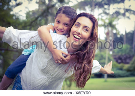 Happy little girl getting a piggy back from mother in the park - Stock Photo
