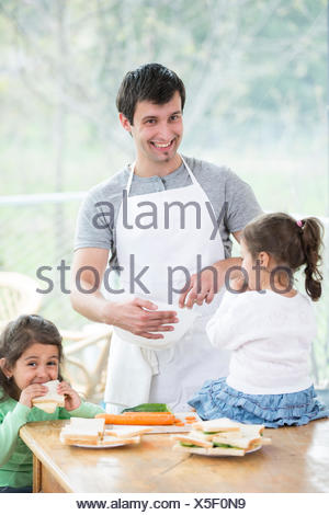 Happy father preparing food with little daughters at home - Stock Photo