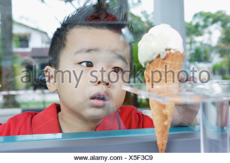 Boy looking at ice cream cone through glass - Stock Photo